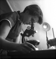 Rosalind Franklin looks through a microscope - black & white