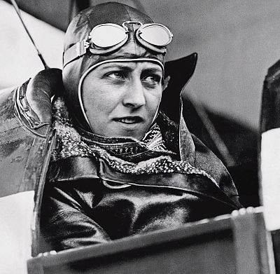 Pilot Amy Johnson in her aeroplane wearing leather jacket, helmet and goggles