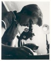 Rosalind Franklin looks through a microscope - black & white