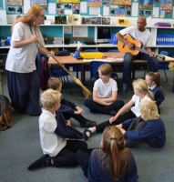 Frances and Herbie perform music for guitar and sweeping brush in a classroom on the Isle of Coll