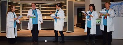 5 singers in lab coats performing at the Science Museum