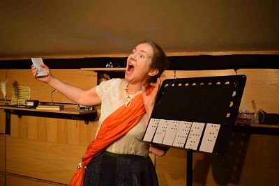 A singer wearing an orange silk sash with playing cards