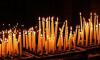 a collection of slim church candles alight in the dark