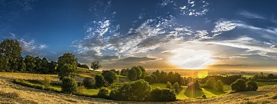 a panorama of the English countryside as the sun goes down