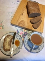 A tea table with bread and a slice buttered with marmalade on the side and a cup of tea on a floral table cloth