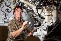 A female engineer in uniform holds a torch to investigate the inner workings of an aeroplane