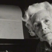 A lady with white hair sitting by some music written on manuscript